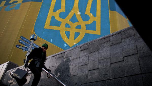 Женщина проходит мимо огромного украинского флага в центре Киева