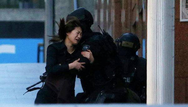 Женщина выбегает из кафе, где неизвестный держит заложников. Сидней, 15 декабря 2014