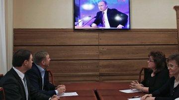 Мэр Калининграда Александр Ярошук (второй слева) смотрит телетрансляцию большой пресс-конференции президента России Владимира Путина
