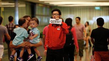 Сотрудник аэропорта Чанги держит табличку с номером пропавшего рейса QZ8501 компании Air Asia