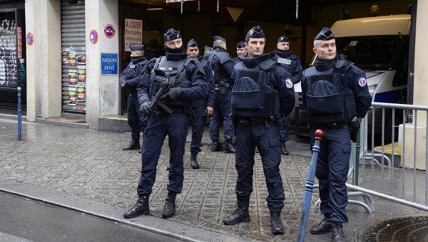 Офицеры французской полиции стоят на страже перед зданием редакции газеты Liberation, куда переехал журнал Charlie Hebdo