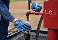 Инженер берет образец нефти на одной из скважин
