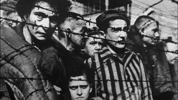 Заключенные за колючей проволокой в концентрационном лагере Освенцим