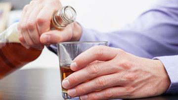 Мужчина держит бутылку с крепким алкоголем. Архивное фото