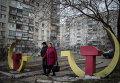 Местные жители проходят мимо скульптур серпа и молота в Мариуполе, Украина