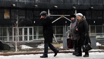Жители Донецка на фоне поврежденного в результате обстрела здания. Архивное фото