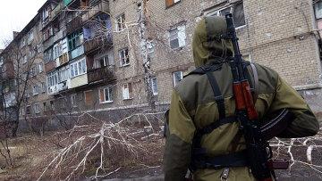 Ополченец у разрушенного в результате обстрела дома в пригороде Донецка. Архивное фото