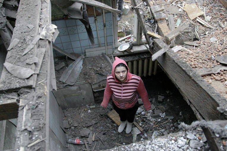 Женщина осматривает разрушенный дом после обстрела Донецка