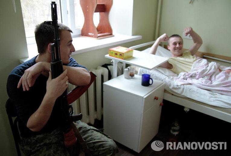Раненый украинский военный общается с охраняющим его ополченцем в одной из больниц Донецка