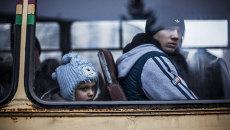 Люди сидят в автобусе, чтобы покинуть зону военного конфликта. Архивное фото