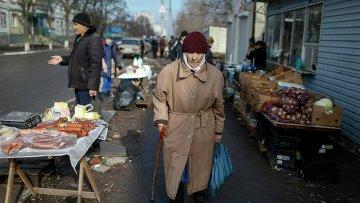 Женщина проходит мимо рынка в Мариуполе 3 февраля 2015