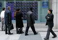 Прохожие в Токио смотрят на экран с биржевыми котировками