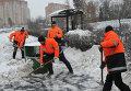 Сотрудники коммунальных служб убирают снег с территории автобусной остановки