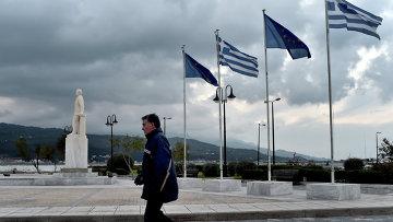 Мужчина проходит мимо флагов ЕС и Греции в порту на острове Самос. Архивное фото