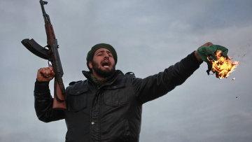 Боец оппозиции сжигает государственный флаг Ливии во время боев за город Рас-Лануф