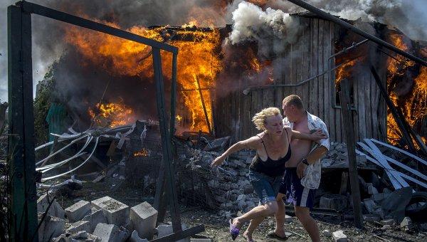 Местные жители спасаются от пожара, возникшего в результате авиационного удара вооруженных сил Украины по станице Луганская. Архивное фото