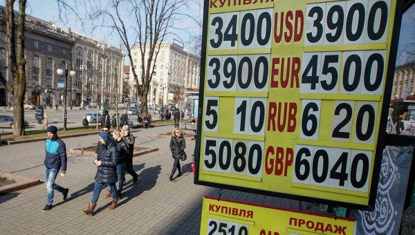 Люди проходят мимо табло с курсом валют в центре Киева 25 февраля 2015. Архивное фото