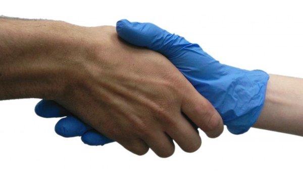 Ученый пожимает руку добровольцу в стерильной перчатке во время эксперимента