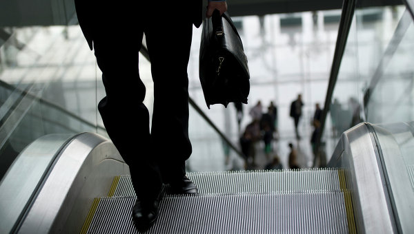 Мужчина с портфелем поднимается по эскалатору. Архивное фото