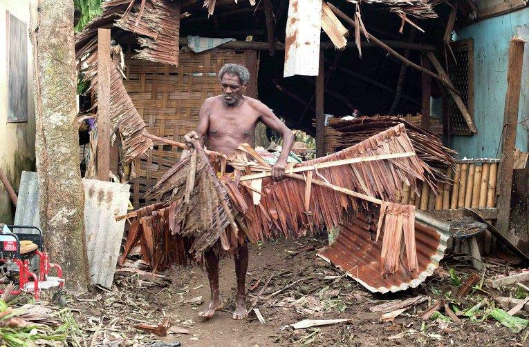 Житель столицы Вануату Порт-Вилы ликвидирует последствия циклона Пэм