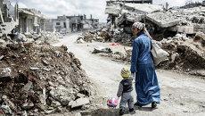 Женщина с ребенком в городе Кобани. Сирия. Архивное фото