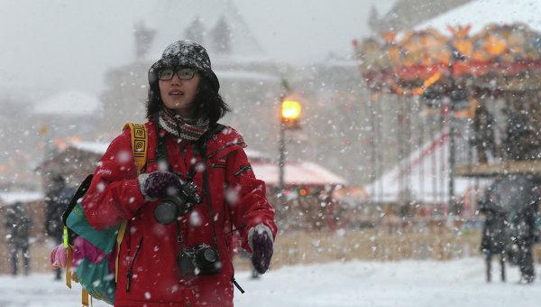 Прохожая на Красной площади во время снегопада в Москве