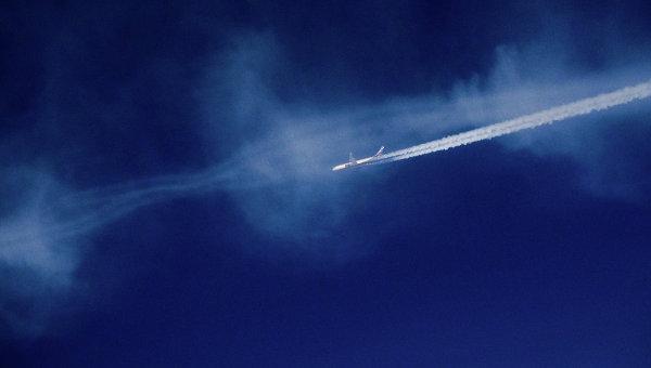 Вид из окна самолета на другой самолет, летящий в небе. Архивное фото