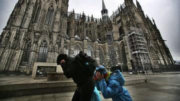 Прохожие возле Кельнского собора во время урагана Никлас, Германия. Архивное фото