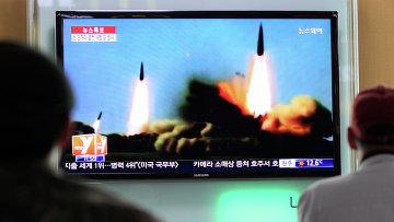 Люди наблюдают за запуском ракет Северной Кореей по телевизору, архивное фото