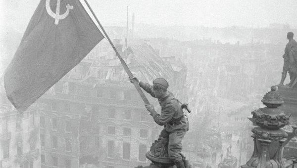 Боец водружает знамя Победы на крыше здания в Берлине