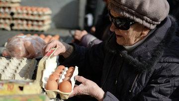 Пенсионерка покупает яйца на городской продовольственной ярмарке в Новосибирске. Архивное фото