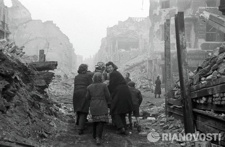 Жители Берлина возвращаются домой по заваленной обломками улице