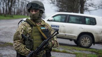 Украинский военный возле машины наблюдателей ОБСЕ возле деревни Широкино. Архивное фото