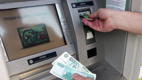 Житель Симферополя снимает наличные денеги через банкомат. Архивное фото