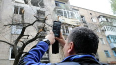 Сотрудник миссии ОБСЕ осматривает дом, поврежденный в результате обстрела Донецка
