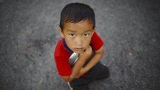 Мальчик стоит возле очереди за едой в Катманду