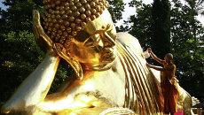 Монах у статуи Будды. Архивное фото