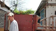 Местный житель у частного жилого дома, пострадавшего в результате обстрела Октябрьского района города Донецка