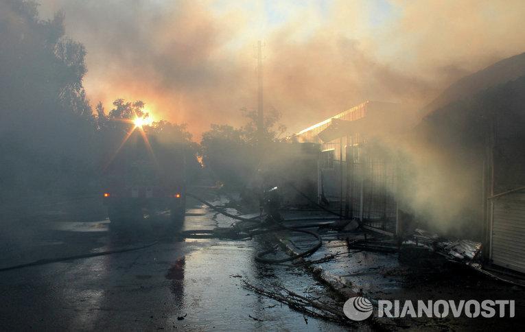 Сотрудники пожарной охраны тушат пожар на рынке Октябрьский, который произошел в результате попадания снаряда во время обстрела города Донецка