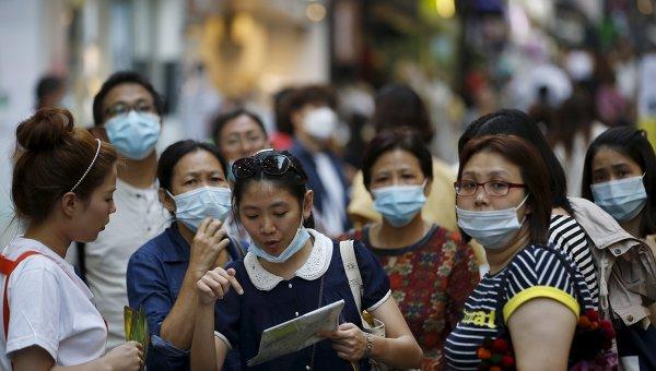 Люди в медицинских масках в центре Сеула, 12 июня 2015