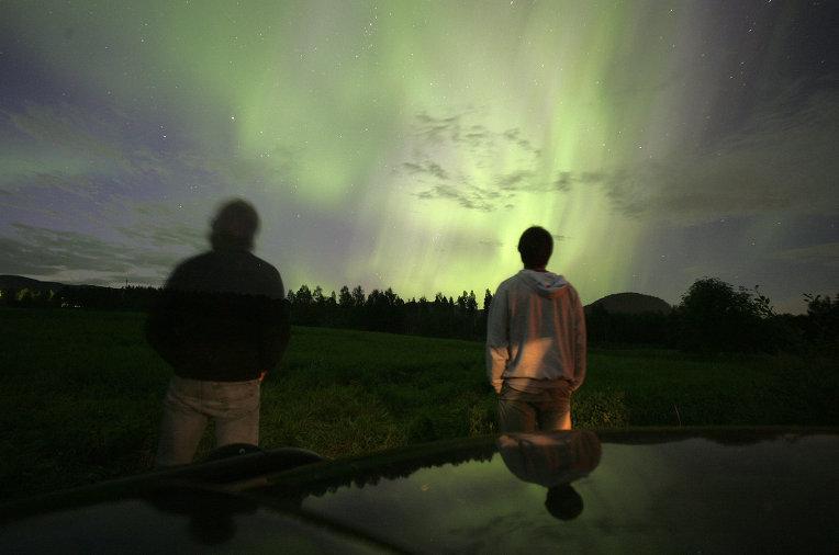 Люди смотрят на северное сияние в Швеции