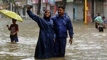 Жители Индии делают селфи на затопленных улицах во время дождя. Архивное фото