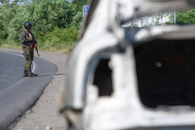 Сотрудник полиции возле сгоревшего автомобиля в Мукачево, Украина