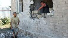 Мужчина ремонтирует стену жилого дома в Горловке после обстрела