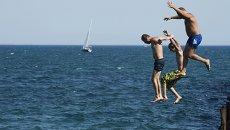 Мужчины прыгают в Черное море в городе Евпатория