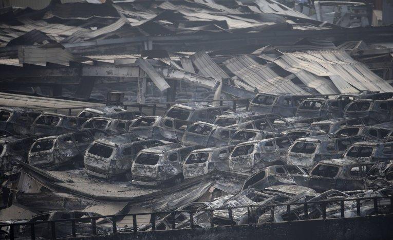 Обгоревшие автомобили на месте взрыва в Тяньцзинь