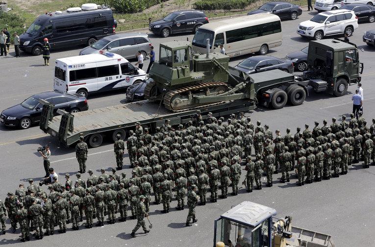 Военная полиция на месте взрывов на складе опасных веществ в промышленном городе Тяньцзинь в Китае