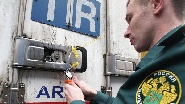 Работник таможенного поста снимает пломбу с прибывшей на терминал фуры. Архивное фото