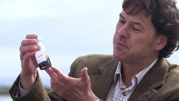 Ученый демонстрирует пробирку с космическим виски