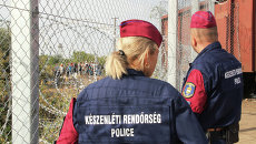 Венгерские полицейские наблюдают за беженцами на сербской стороне. Архивное фото